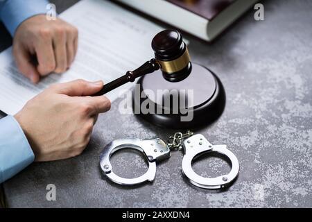 Close-up d'un juge Part Substitution Gavel avec des menottes sur 24, dans la salle d'audience Banque D'Images