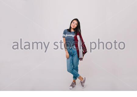 Portrait complet du modèle féminin à poil sombre dans un pantalon denim. Jolie fille brunette en Jean et t-shirt tendance posant en studio sur fond blanc. Banque D'Images