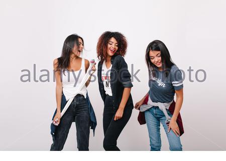 Une fille africaine insouciante s'amuser avec des amis à la mode souriant en studio. Modèle féminin noir excité debout sur fond blanc avec les yeux fermés tandis que les femmes de brunette dansent à côté. Banque D'Images