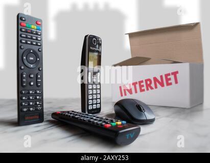 Sur une surface claire, nous voyons une télécommande pour la diffusion en continu, une autre pour la télévision, une souris d'ordinateur et une boîte qui représente le paquet de services. Banque D'Images