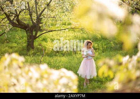 Jeune fille attirante promenades dans le parc vert printemps profiter de la floraison de la nature. Smiling girl sain de tourner sur la pelouse au printemps. Sans allergie. Banque D'Images
