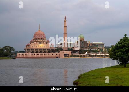 Reflet de la Mosquée Putra et du Jabatan Perdana Menteri sur le lac Putrajaya au crépuscule. Banque D'Images