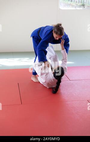 Judokas pratiquant le judo pendant un sparing dans une salle de sport