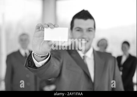 Jeune homme d'affaires tenant une carte blanche avec des collègues en arrière-plan Banque D'Images