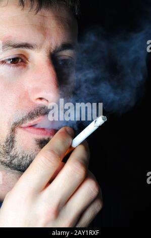Homme fumeur dans l'obscurité
