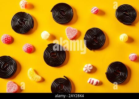 Spirales de réglisse avec des bonbons fruités de jub entre dispersés sur un fond jaune dans un motif décoratif de la tête