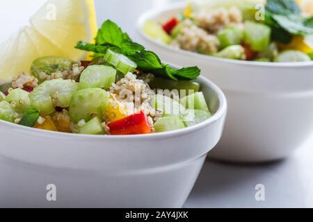 Bol de légumes sain, salade de quinoa avec céleri frais, poivrons, herbes et tranche de citron, gros plan, nourriture à base de plantes Banque D'Images