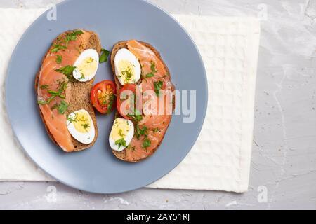 Sandwich au saumon frais avec œufs de caille sur une plaque de gros plan, vue de dessus Banque D'Images