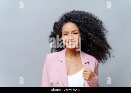 Une femme ébridée à la peau foncée et positive avec des cheveux lumineux, porte une veste violette formelle, pose sur fond gris avec un espace vide, heureuse de rencontrer b Banque D'Images