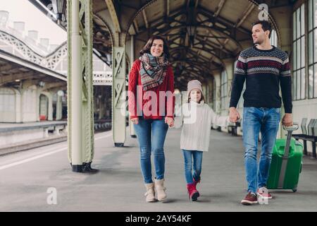 Une femme heureuse brunette porte un pull et un foulard rouges, un petit enfant dans un grand pull, un homme de main porte une valise, retour de voyage ensemble, pos express Banque D'Images