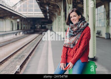 Heureuse jeune femme européenne porte le pull rouge, le foulard, tient le téléphone mobile, se tient dans le sac, aime voyager, pose à la gare, sourires heureux. Personne Banque D'Images