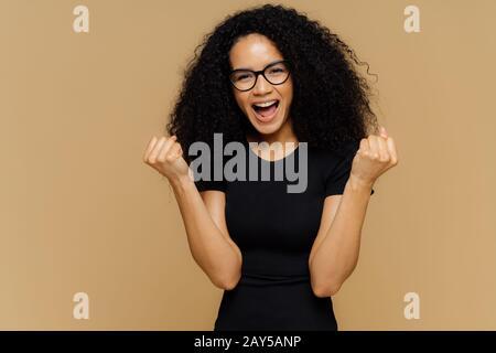 Oui, je l'ai enfin fait ! Une jolie femme à la peau sombre et optimiste soulève des poings serrés, exclame des émotions positives, célèbre la victoire, habillée Banque D'Images