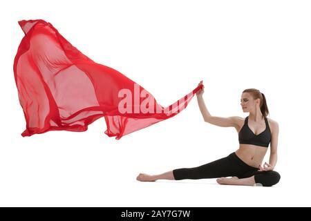 Jolie fille faisant du yoga posant avec tissu rouge Banque D'Images