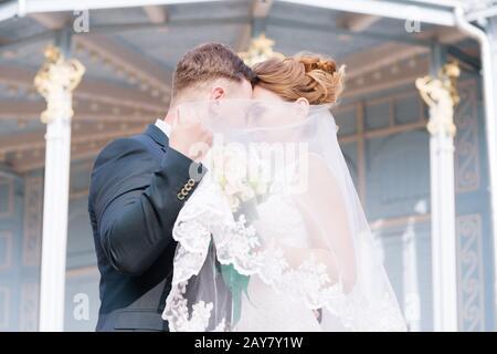 Portrait d'un beau couple de jeunes mariés, se cachant derrière un voile, s'embrasse contre l'arrière-plan du bâtiment d'époque Banque D'Images