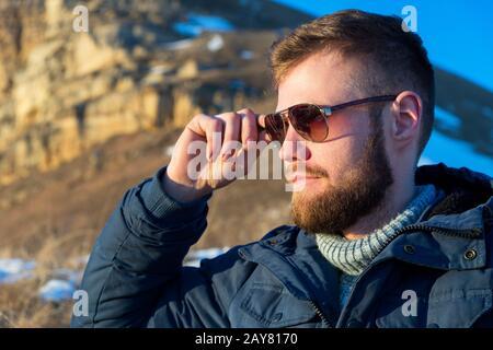 Gros plan Portrait d'un voyageur de Hipster Grave et sérieux avec une barbe dans des lunettes de soleil dans la nature. Banque D'Images