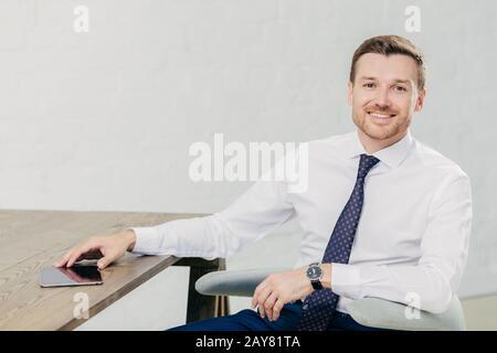 Photo de posive jeune entrepreneur masculin réussi vêtu d'une élégante chemise blanche avec cravate, regarde positivement l'appareil photo, a la pause après le travail, me pose Banque D'Images
