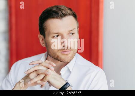 Une photo horizontale de pensive beau jeune travailleur d'entreprise masculine tient les mains ensemble, se tient de côté, étant profondément dans les pensées après la réunion, pose sur re Banque D'Images