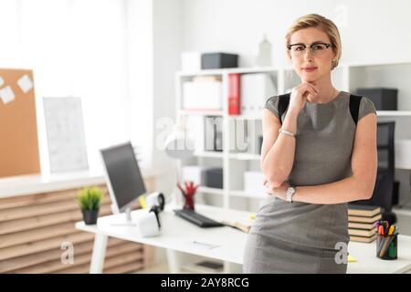 Une jeune fille à lunettes se tient près d'une table dans le bureau. Banque D'Images