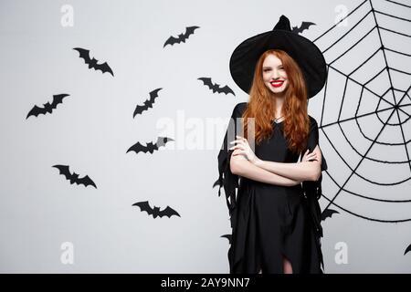 Sorcière Halloween concept - Happy Halloween sorcière holding posant sur fond gris foncé studio avec chauve-souris et araignée. Banque D'Images