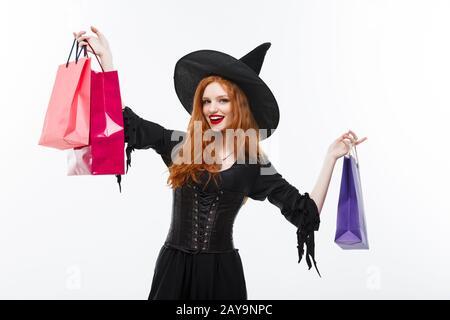 Sorcière Halloween concept - Happy Halloween sorcière smiling and holding shopping bags colorés sur fond blanc. Banque D'Images