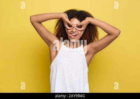 Fun and People concept - Headshot Portrait de heureuse femme afro-américaine Alfo avec des freckles souriant et des lunettes de doigts.