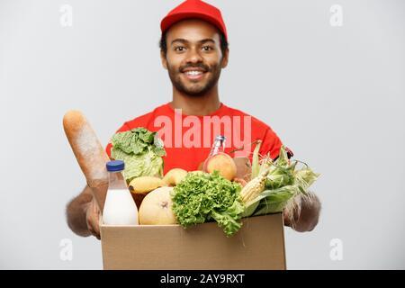 Concept de livraison - Beau homme de livraison afro-américain transportant boîte de paquet de nourriture et de boisson d'épicerie de magasin. Isolé le Banque D'Images