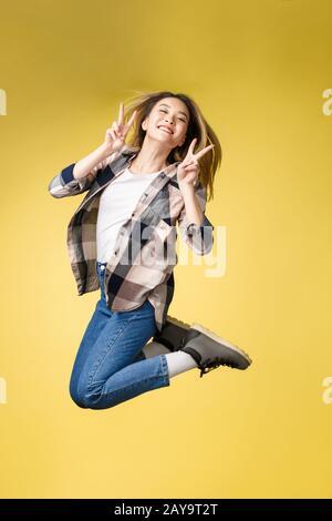 Vertical pleine longueur de corps studio photo portrait de jolie négligence heureuse dame étudiant montrer sa marque V-Sign près de e Banque D'Images