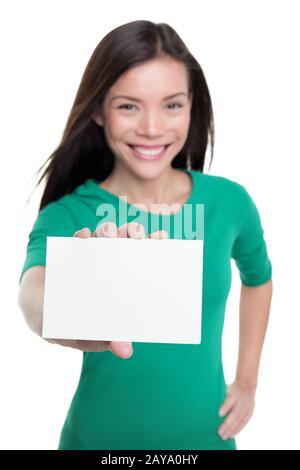 Heureuse femme asiatique montrant un signe de carte de visite blanche. Jeune fille décontractée tenant le papier blanc pour le texte publicitaire copyspace. Banque D'Images