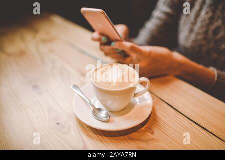 les mains près d'une belle jeune fille utilise, types de texte sur un téléphone mobile à une table en bois près d'une fenêtre et boire du café dans Banque D'Images