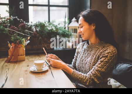belle jeune fille utilise, types de texte sur un téléphone mobile à une table en bois près de la fenêtre et boissons café dans un café décoré Banque D'Images