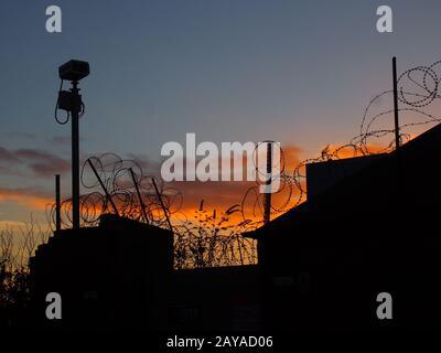 barbelés fil et caméra de sécurité sur un mur avec ciel et coucher de soleil en soirée