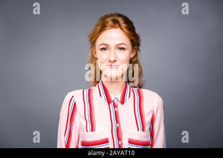 portrait d'une jeune fille à poil rouge dans le studio sur un fond gris isolé. Une femme se tient debout et sourit dans une feuille rouge Banque D'Images