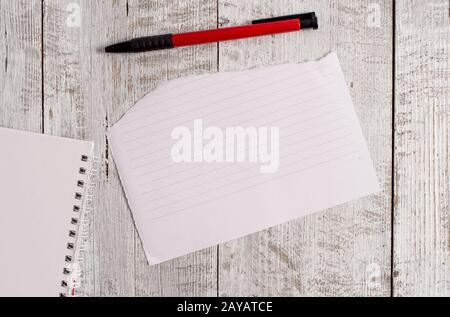 Papier déchiré et feuille d'ordinateur portable plus un stylo placé sur une table en bois. La papauté fixe s'adhère à la toile de fond classique en position inclinée Banque D'Images