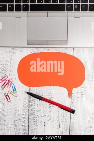 Demi-vue ordinateur portable ouvert tendance vide bulle de parole face vers le bas stylos de couleur clips allongé vintage table en bois. Calcul personnel Banque D'Images
