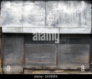 l'avant d'un magasin abandonné dans une rue avec des volets métalliques sales et sales fermés au-dessus de l'avant et de la porte du magasin