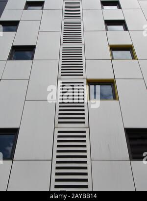 gros plan sur des panneaux en métal argenté sur un bâtiment moderne avec fenêtres répétées et grille géométrique Banque D'Images
