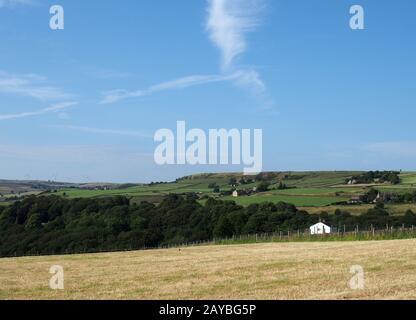 un pré de foin d'été coupé entouré de champs verts et de fermes avec un ciel bleu ensoleillé au-dessus du village de ludddenden dans la calde