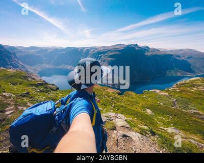 Lac Ringedalsvatnet Près De Trolltunga. Lac Blue En Norvège. Femme touriste en chapeau et sac à dos se tient à l'arrière et tient l'appareil photo en han Banque D'Images