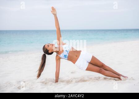 Côté planche yoga forme physique fille d'entraînement équilibre renforcer les muscles abs et le poignet, tonifiant le corps avec l'entraînement de noyau à l'extérieur sur la plage. Femme asiatique faisant de l'exercice de poids corporel. Banque D'Images