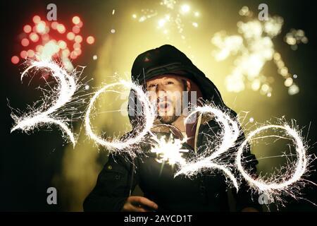 Homme célébrant la Saint-Sylvestre avec des feux d'artifice et écrivant les numéros 2020 avec un sparkler pendant une exposition prolongée photograp