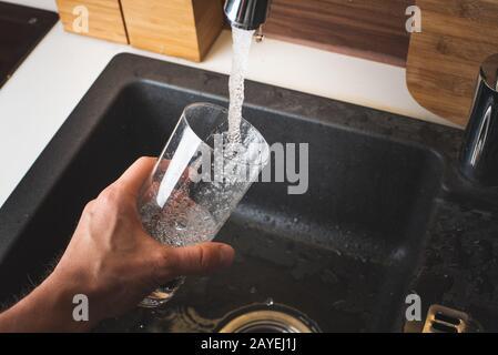 Le remplissage de l'eau de robinet de cuisine en acier inoxydable. Concept de l'eau potable Banque D'Images