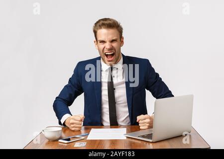 Un jeune homme d'affaires blond expressif et indigné a fait une table agressive et a crié un partenaire commercial, se sentant déçu Banque D'Images