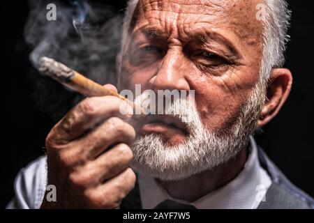 Portrait de l'homme senior sérieux qui sauve le cigare.