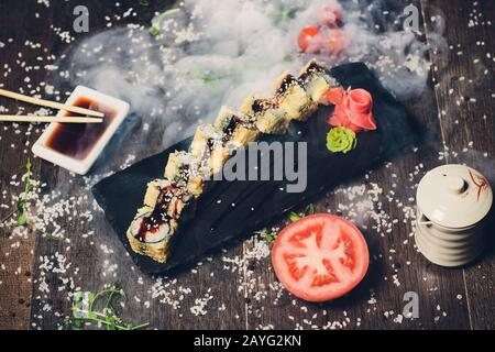divers sushis sur plaque blanche avec baguettes sur fond en bois