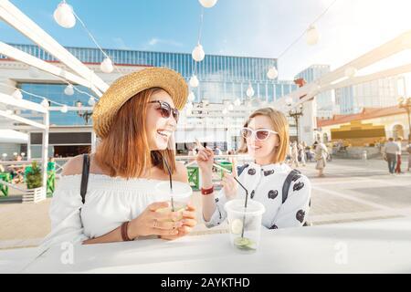 Deux filles de race mixte communiquent et rigolent dans un café avec des boissons rafraîchissantes. Le concept de l'amitié et des relations entre les femmes Banque D'Images