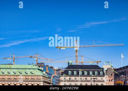 16 septembre 2018: Stockholm, Suède - grues travaillant au-dessus des toits historiques de la vieille ville. Banque D'Images