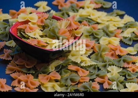 Tas de pâtes à noeud multicolores sur fond bleu Banque D'Images