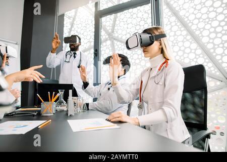 science, technologie future, médecine et chimie concept - jeunes médecins multiraciaux ou scientifiques en blouses de laboratoire blanches et verres vr travaillant avec Banque D'Images