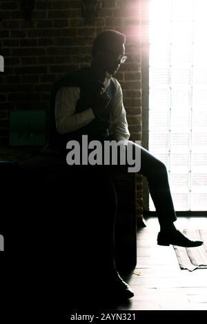 portrait du jeune homme africain pensif américain dans des lunettes et une veste bleue
