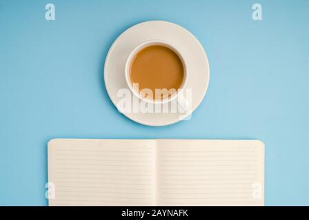 Cahier blanc ouvert pour les notes, une tasse de café blanche avec du lait sur un fond bleu, placez pour le texte Banque D'Images